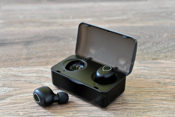 Generic Black wireless earbuds in a charging case on a wood background. (logos and labels removed)