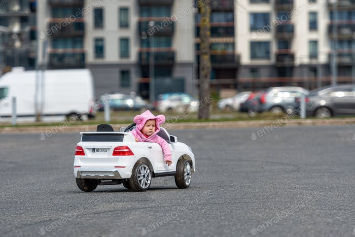 little girl drives a big white childrens electric toy car in the parking lot at the residential home