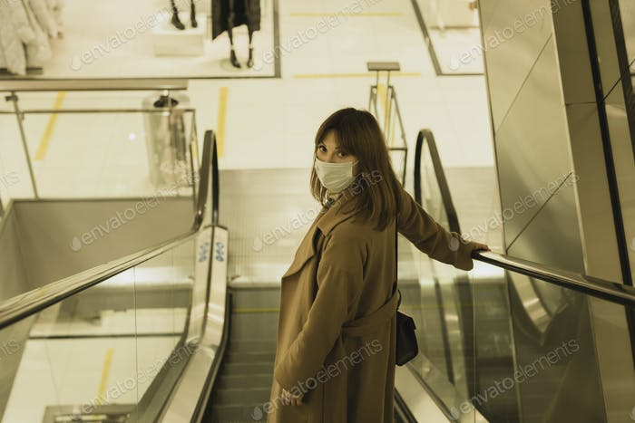 Red-haired young woman in a coat and mask in a shopping center on an escalator in a public place