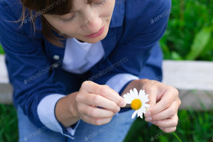 Beautiful young woman in a blue shirt is guessing on a camomile outdoors on a sunny summer day.