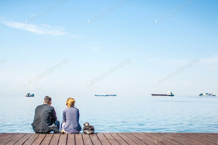 Friends Sitting On The Dock Talking And Enjoying The View