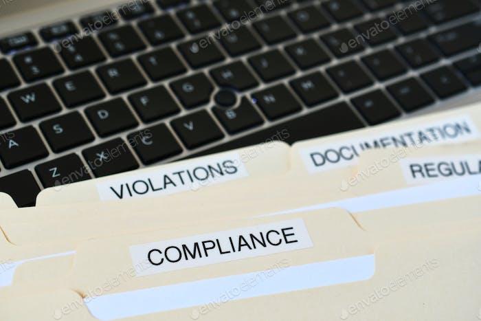 Dateiordner mit Wörtern Compliance, Verstöße, Dokumentation auf schwarzer Computertastatur