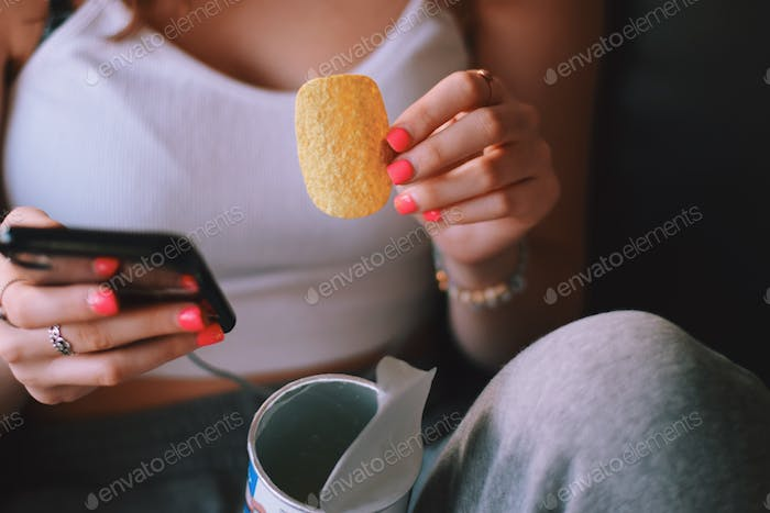 Young teenage girl sitting on a couch, eating potato chips and using mobile phone