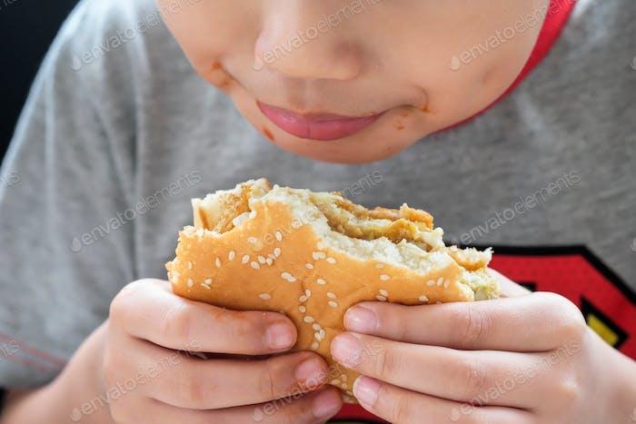 Nahaufnahme von hungrigen Kind essen einen Huhn Burger. Flache Tiefe des Urlaubs.