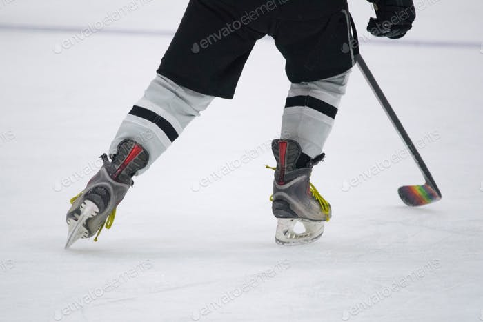 Close up of ice skates and a hockey stick with rainbow tape