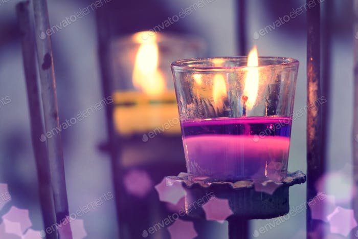 Purple light candle in glass and abstracts blur background
