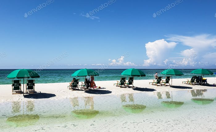 Tourists sitting in green beach chairs with the green umbrellas watching the tide roll in....