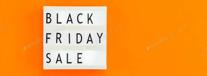 Creative Top view flat lay promotion composition Black friday sale text on white lightbox orange