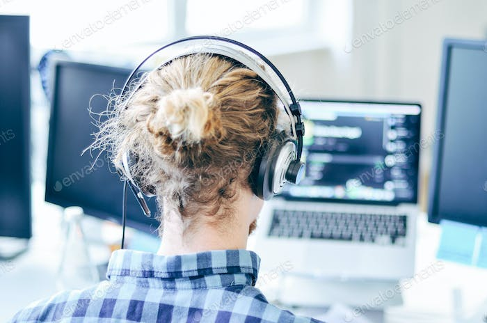 Man using laptop and listening to music