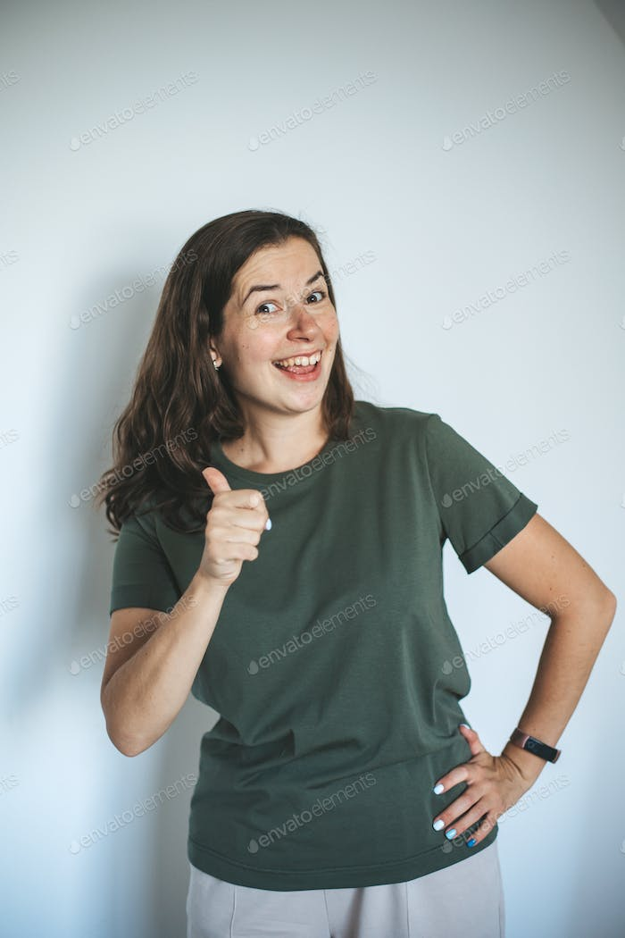 Stylish young woman in blank green t-shirt on white background