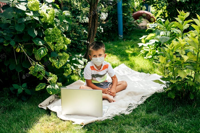 Boy in medical mask sitting on grass in garden and doing homework. Online education