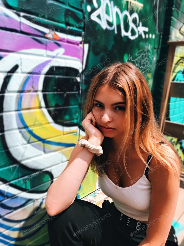 Young teenage girl sitting on the steps in the graffiti alley