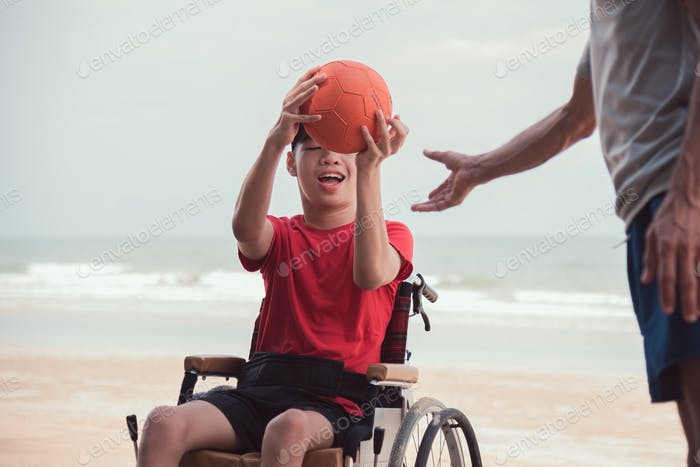 Ball in hands of happy disabled teenage boy, Activity outdoors with father on the beach background.
