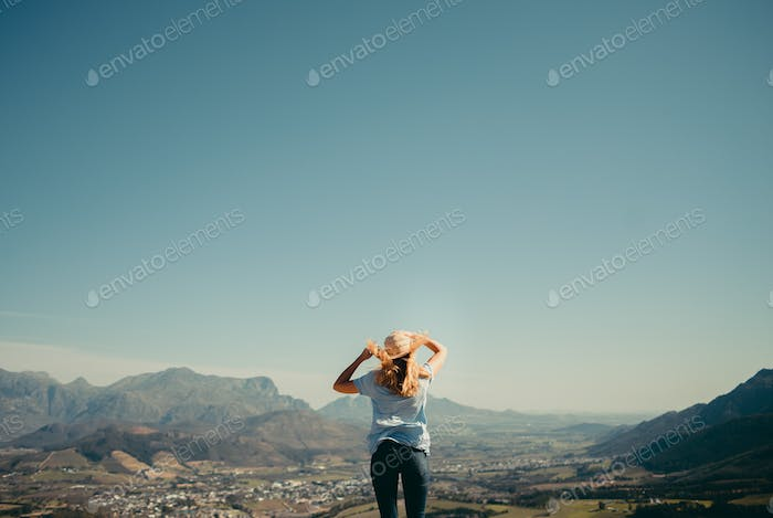 Young woman standing on top of the world