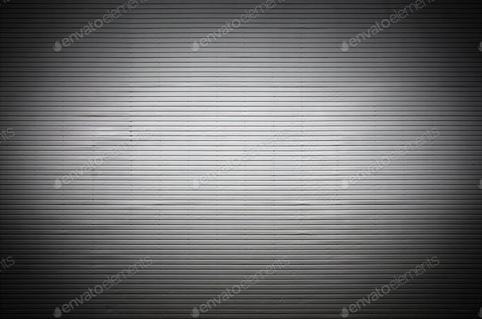 Die Textur einer Metallwand oder einer Oberfläche aus Wellblech mit unsichtbaren Lichtquellen, die