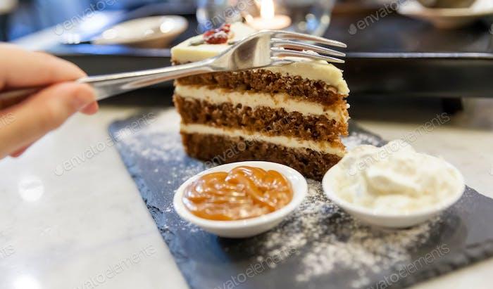 Enjoying piece of carrot cake, hand in frame