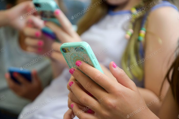 Preteen girls on their phones