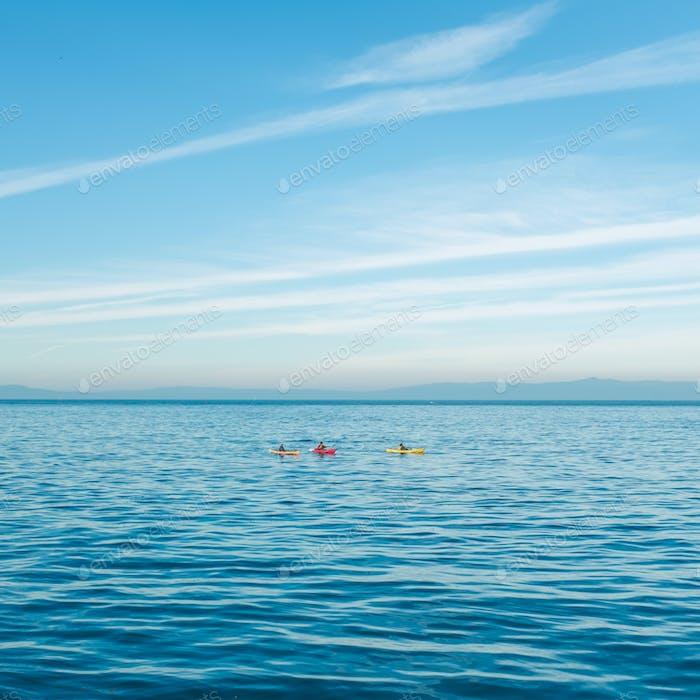 Kayakers paddle along the California coast.