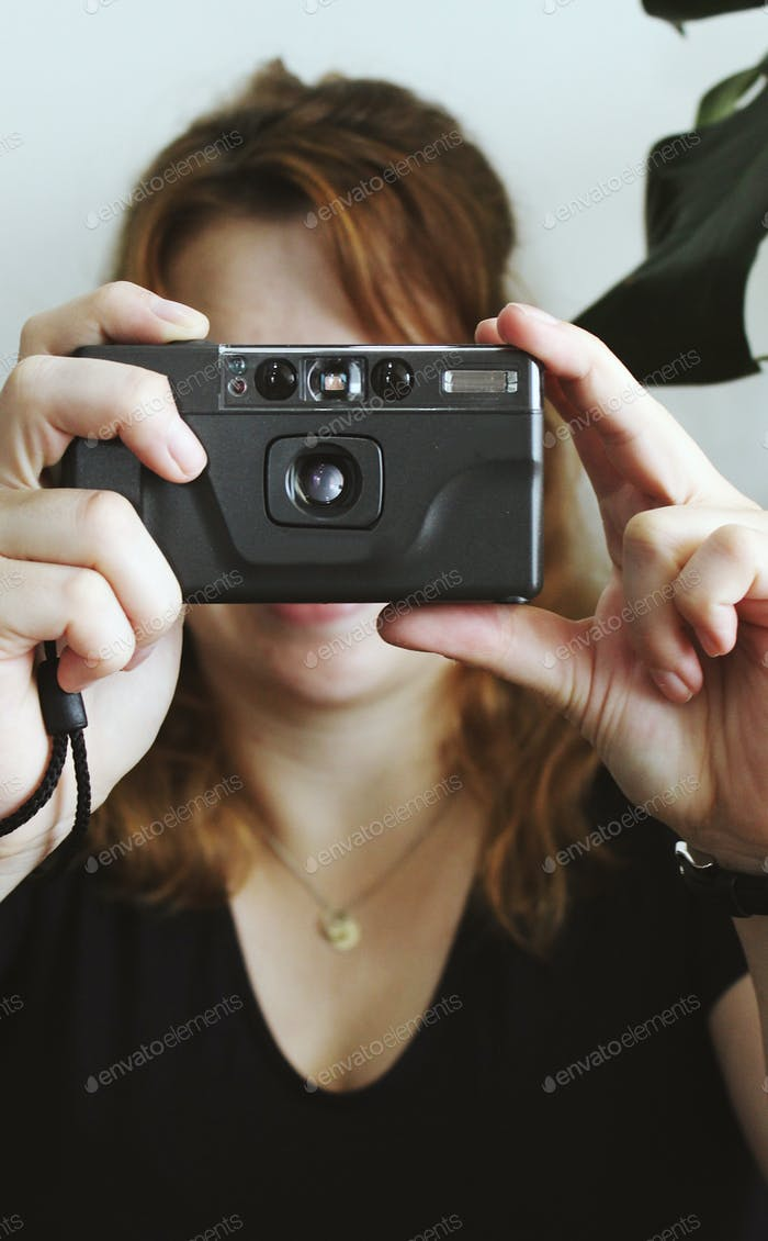 Woman taking picture with retro analog camera
