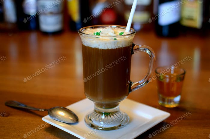 Irish Coffee made with Irish Whiskey in a shot glass for St. Patty's Day on bar with liquor bottles