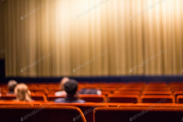 people in the movie theater with red seats - at the cinema and theater