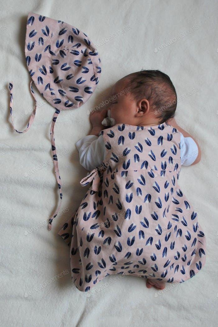 Cute babygirl  (newborn) sleeping next to handmade bonnet
