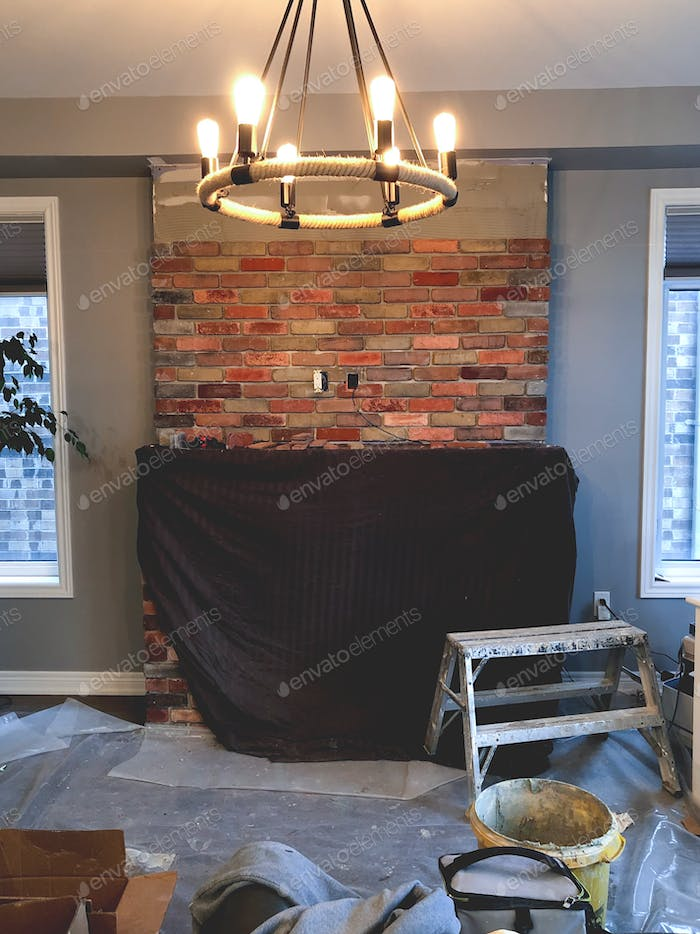 Tiling up fireplace with brick veneer