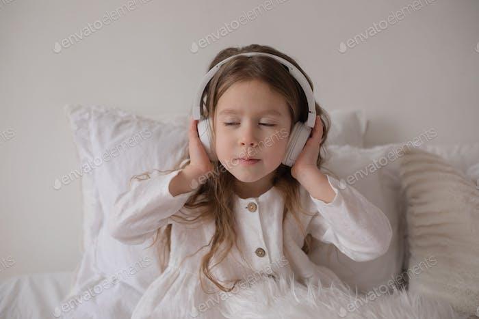 Little girl in headphones listens to music.