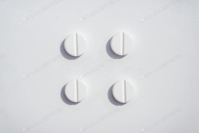 Four white pils on the white background tidy organized. Paracetamol