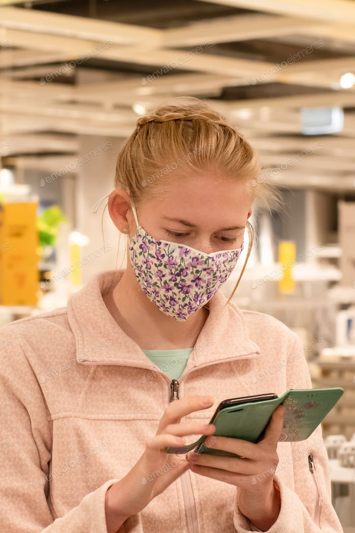 Girl wearing face mask with mobile phone at the store. Covid-19 outbreak. Mandatory face masks