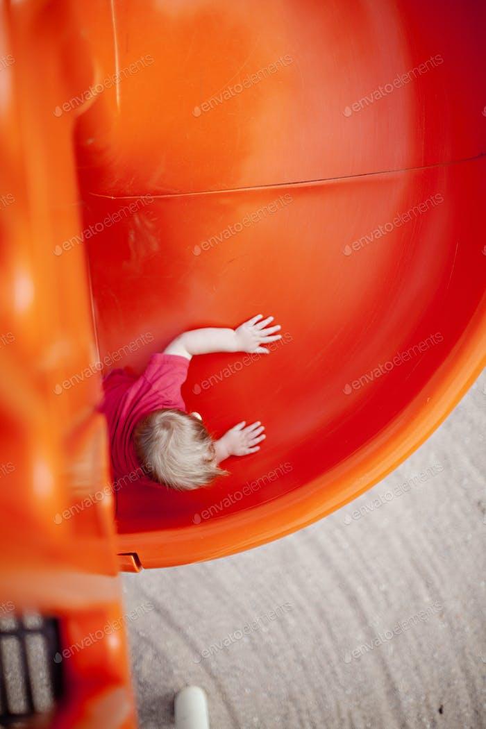 Toddler slides down a circular orange slide at the park wearing a red shirt