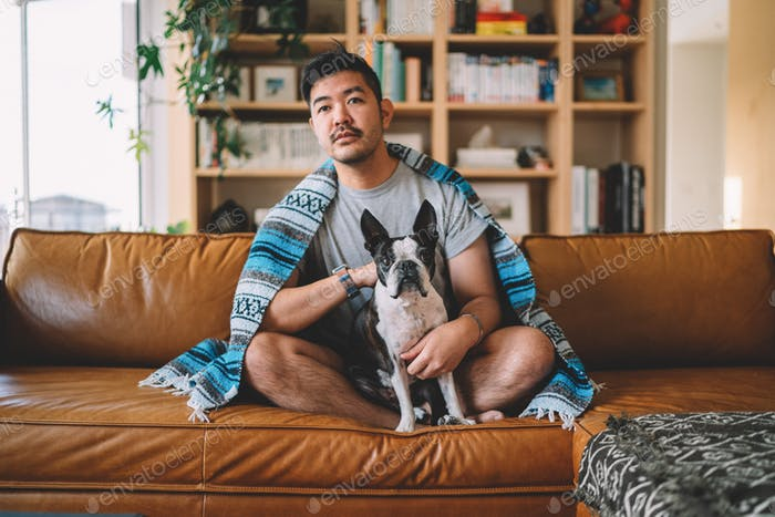 Guy sitting on couch, lounging with his dog watching TV with a blanket.