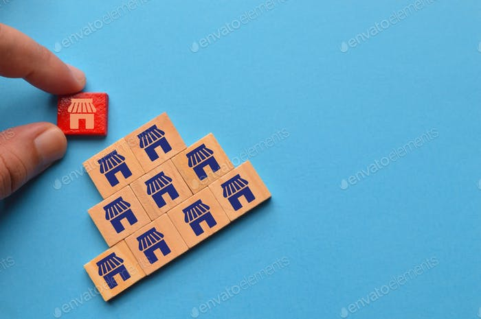 Man hand picked wooden block with store icons. Business empire and franchising concept