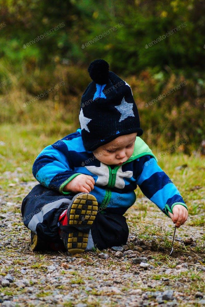 Cute boy digging with a teaspoon