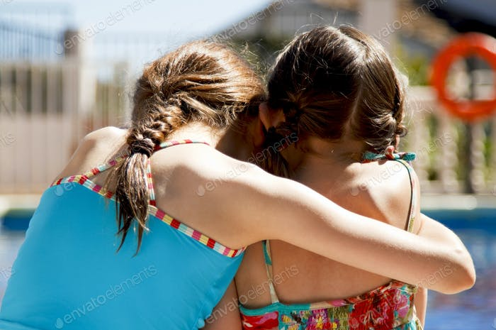 Two girls embracing by the pool, little sisters fall out and make up. Upset but loving.