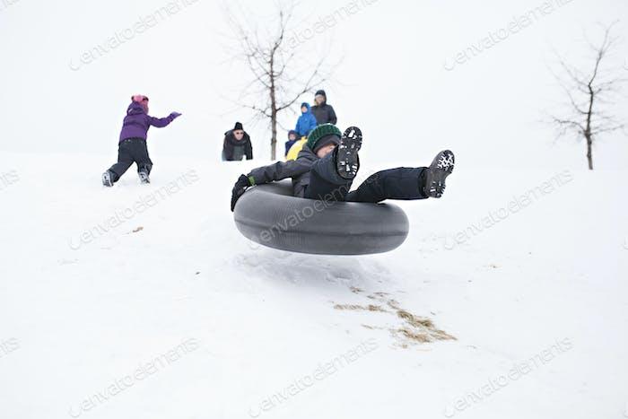 Kinder spielen im Schnee mit voller Schneeausrüstung und Rodeln auf Hügeln