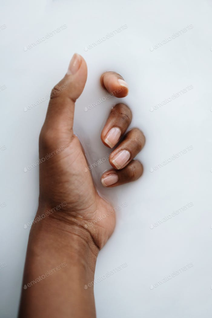 Dark skin hands submerged into milky like water substance