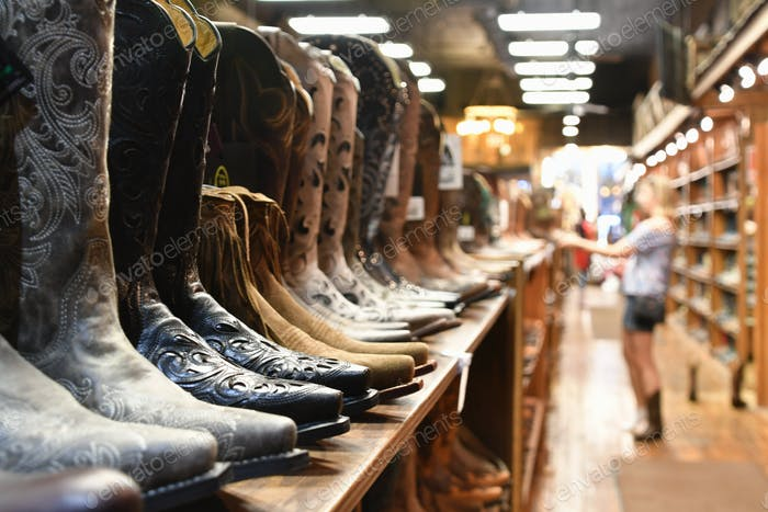 A woman shopping for cowboy boots in a retail shoe store in Nashville, TN