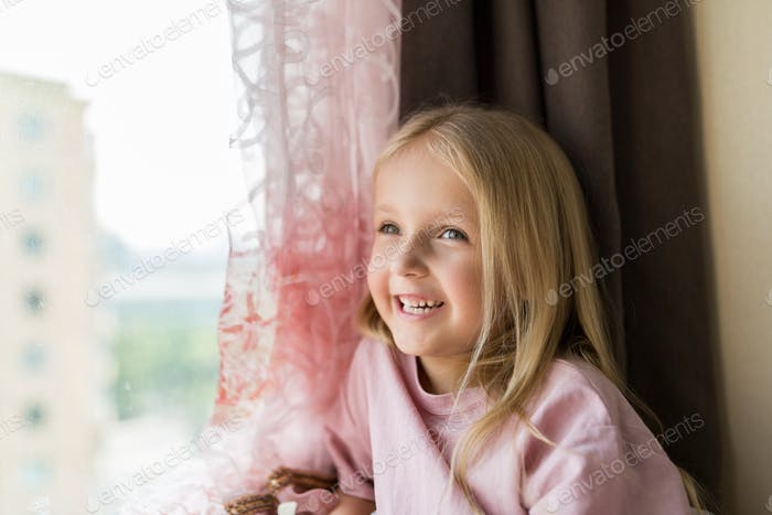 Nominated   Cute little girl with blonde hair sitting near window at home and dreaming. Good day, ha