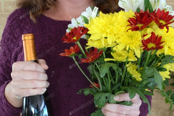 Holding a bottle of wine and bouquet of flowers to give as a hostess gift.