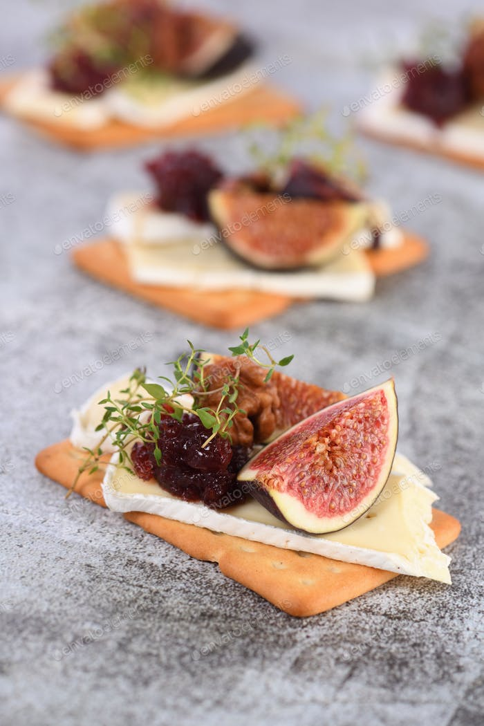 Cracker with a slice of camembert with confiture and figs