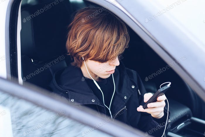The young man listens to music in earphones in the car
