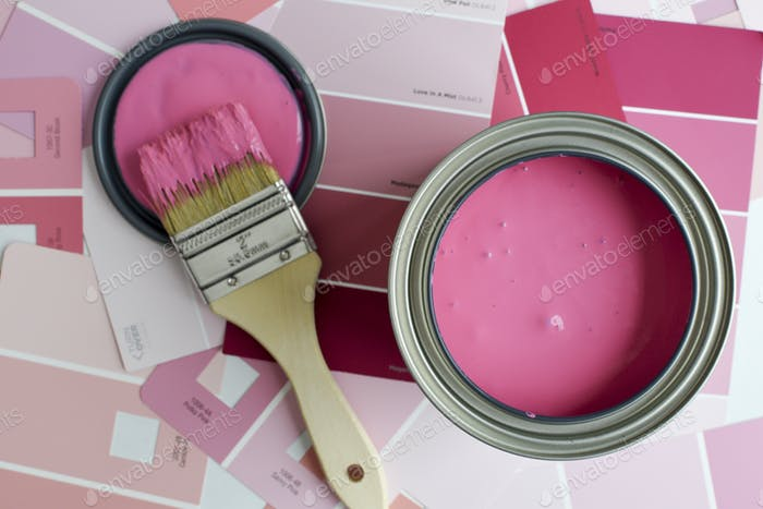 Open can of pink paint with a paintbrush and pink paint swatches