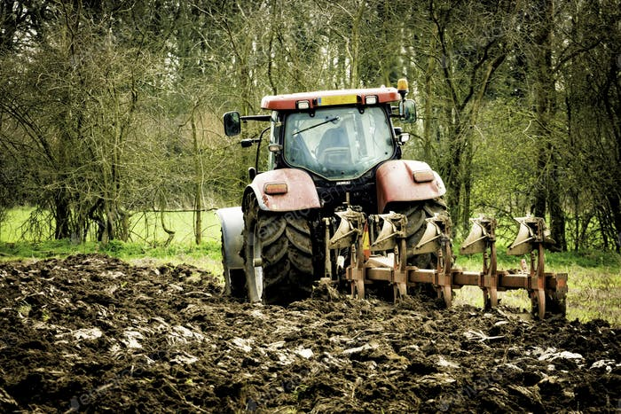 Agricultural tractor ploughing field