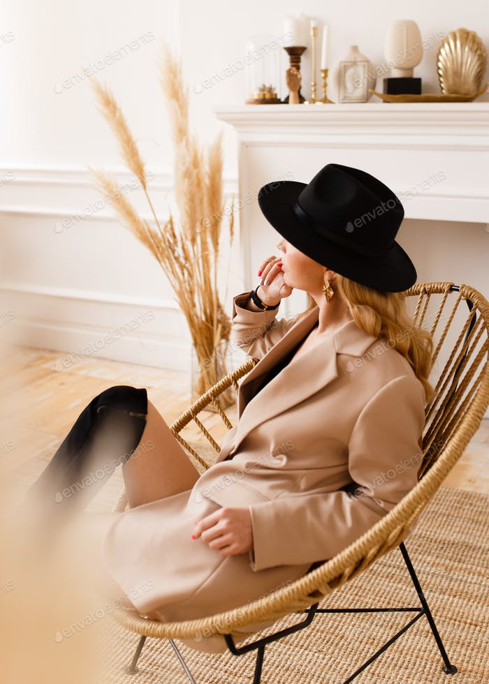 A beautiful attractive fashionable sexy sensual blonde woman in a black hat