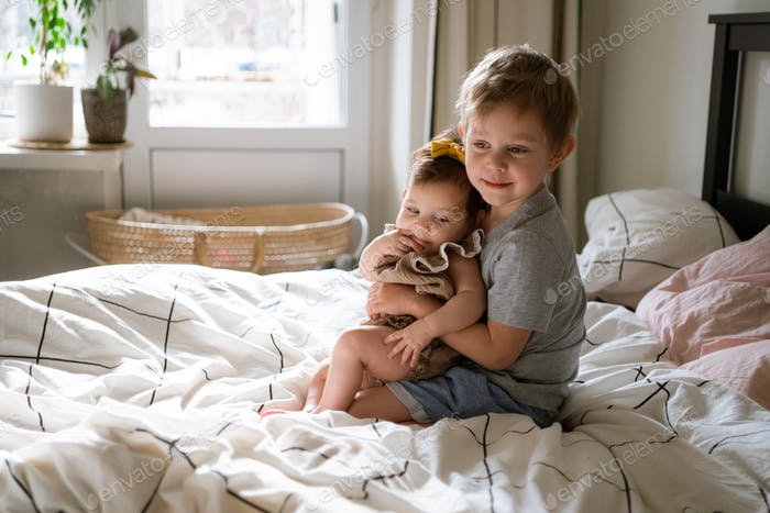 Toddler boy with infant sister sitting on bed