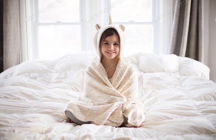 Kid with unicorn blanket on bed
