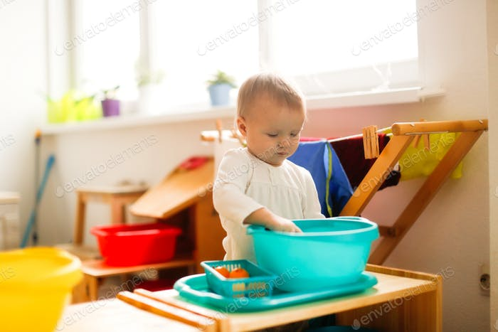 Toddler child  plays with water in a basin,