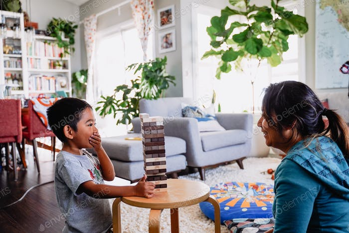 Young diverse boy mom mother child kid family staying at home shelter distance learning board game f