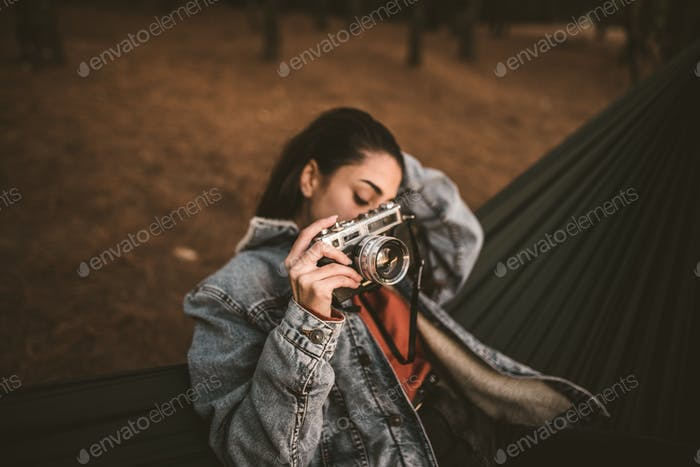 A young woman seated on a hammock holding a camera